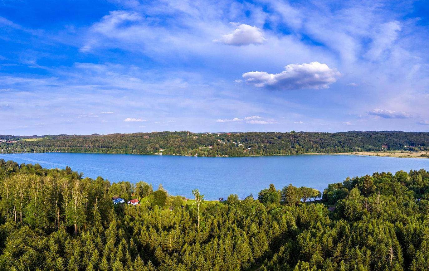 Blick auf den Pilsensee mit Wald im Vordergrund.