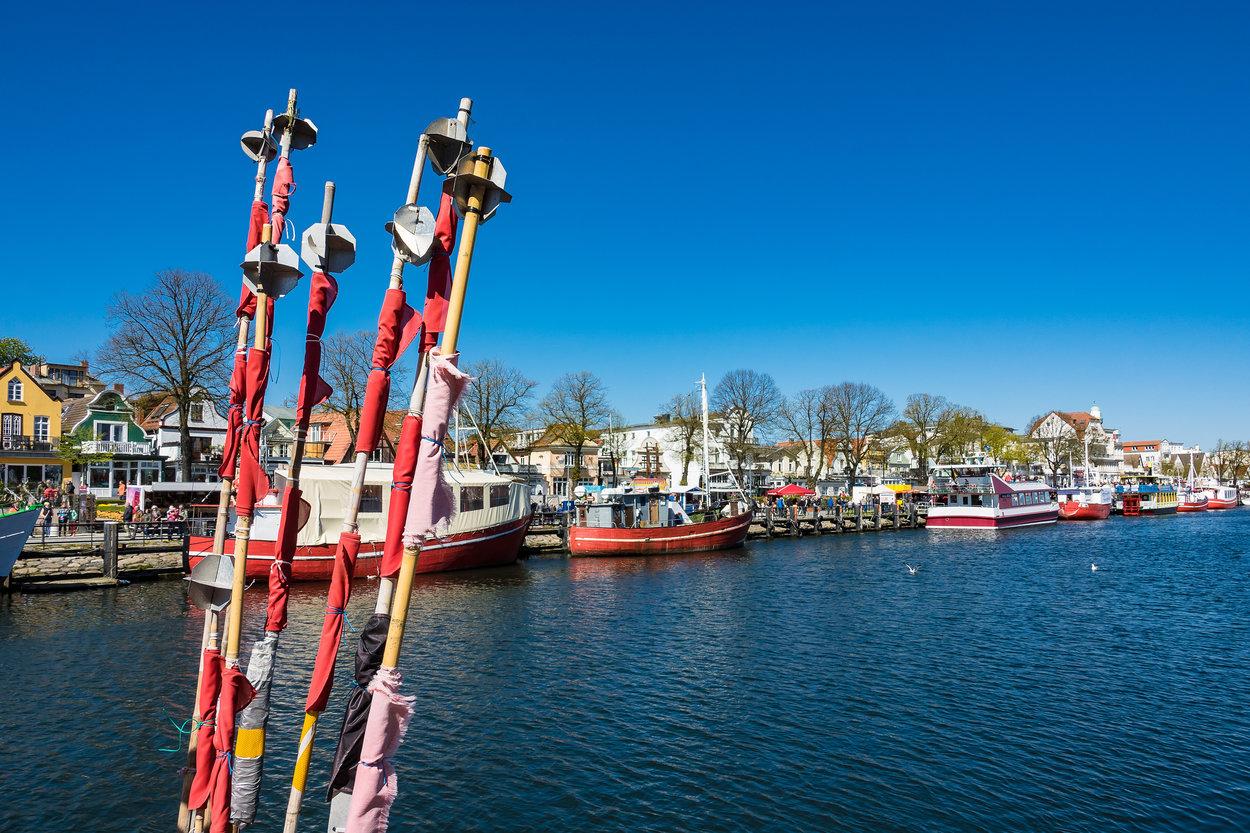 Fischerboote im Hafen von Warnemünde mit Angelgerät im Vordergrund.