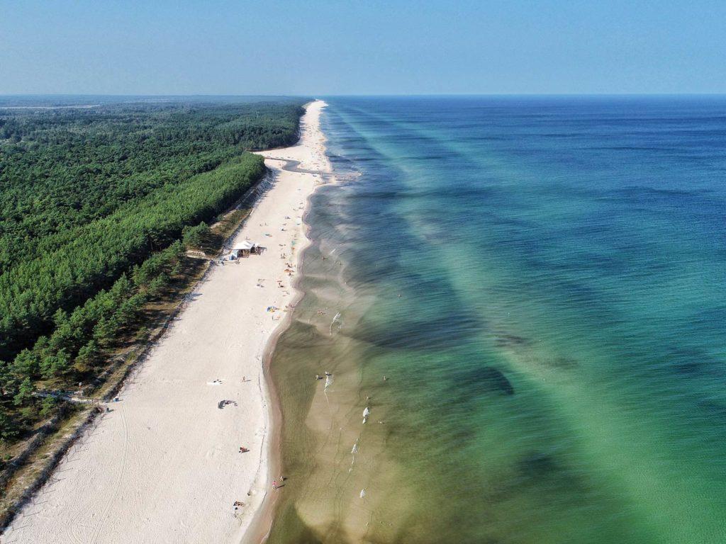 Ostseestrand in Polen mit Wald links und dem Meer auf der rechten Seite.