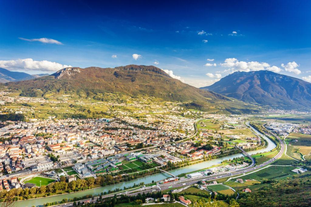 Ein Luftbild von Trient in Italien, mit der quer verlaufenden Etsch.