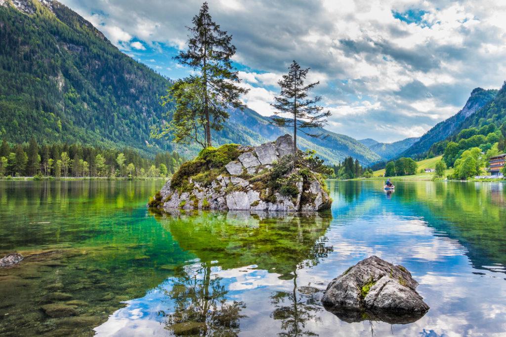 Blick auf einen großen Felsen im Hintersee, auf dem zwei Nadelbäume wachsen, mit den Alpen im Hintergrund.