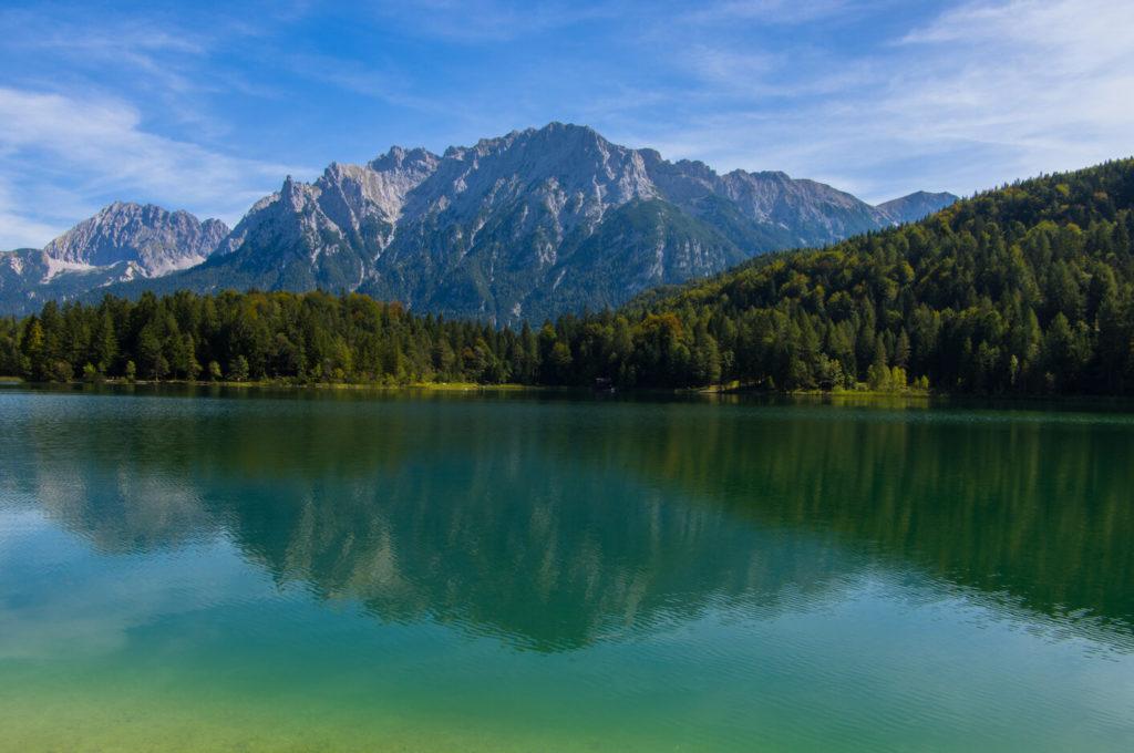 Der Lautersee bei Mittenwald mit seinem grünen Wasser im Vordergrund, Wald dahinter und Bergen im Hintergrund.