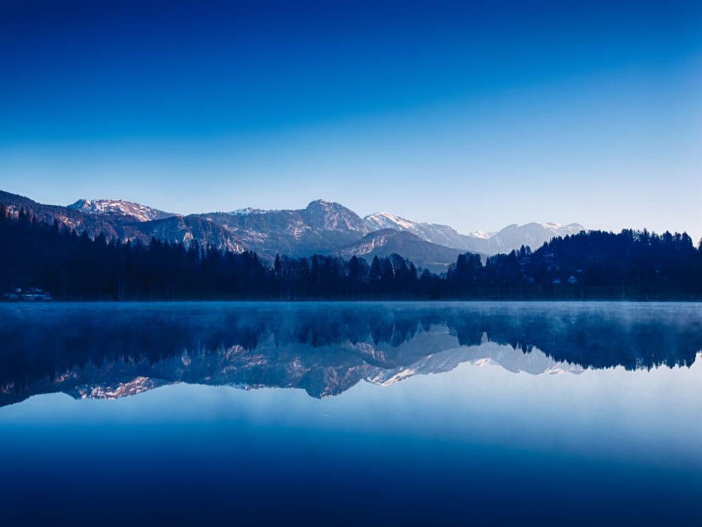 Die vordere Hälfte des Bildes wird vom blauen Wasser des Putterersees eingenommen. Im Hintergrund sind die Alpen zu sehen.