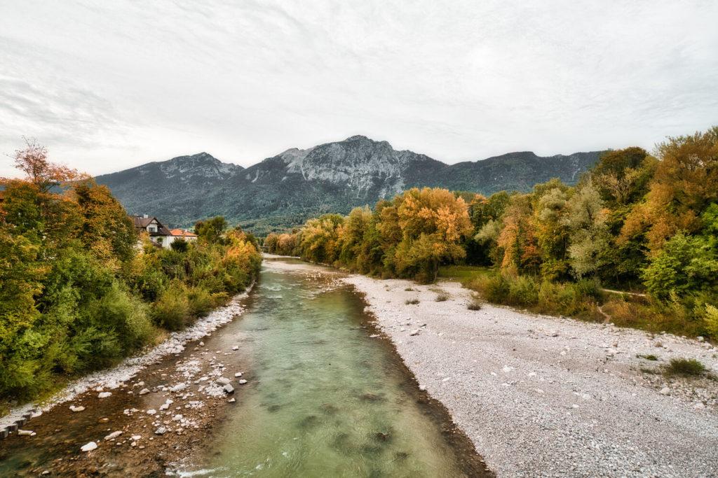 Die Saalach fließt von vorne nach hinten durch das Bild. Rechts ist ein Kiesstrand zu sehen und im Hintergrund sind Berge.