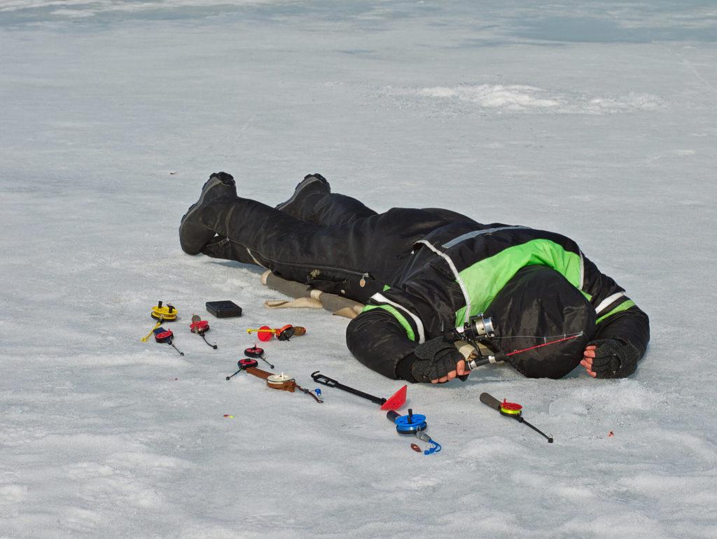 Ein Eisangler in Finnland liegt auf dem Bauch, um die Fische unter dem Eis zu sehen.