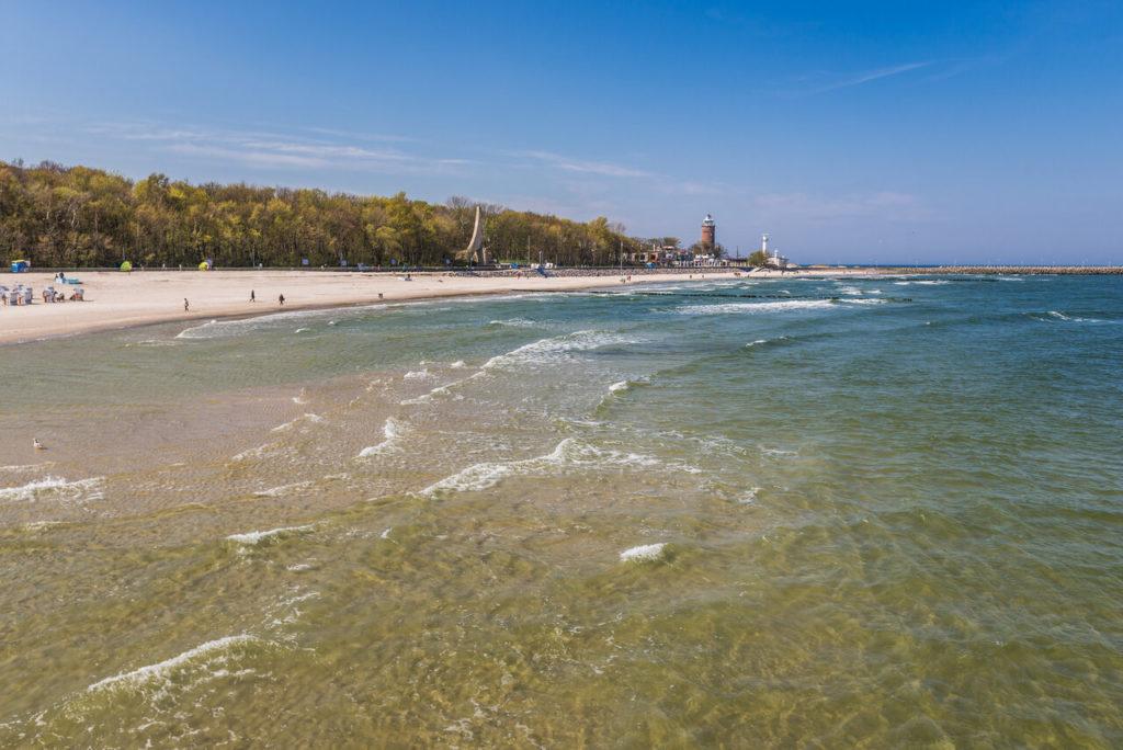 Der Strand von Kołobrzeg, mittig im Hintergrund ist der alte Leuchtturm zu sehen.
