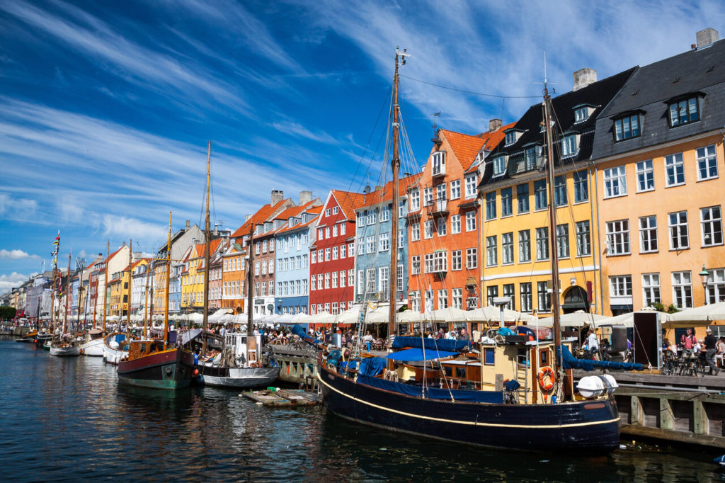 Bunte Häuserfassaden in Kopenhagen. Davor liegen Segelboote in einem Kanal.