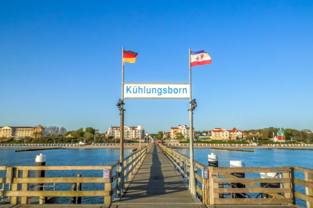 """Blink auf Kühlungsborn vom Steg aus. Über dem Steg hängt ein Schild mit der Aufschrift """"Kühlungsborn."""" Darüber wehen zwei kleine Flaggen im Wind, die Deutsche Flagge und die Flagge Mecklenburg-Vorpommerns."""