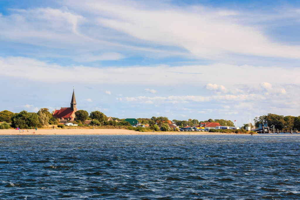 Blick vom Wasser auf den Strand von Schaprode. Links ist die Kirche zu sehen.