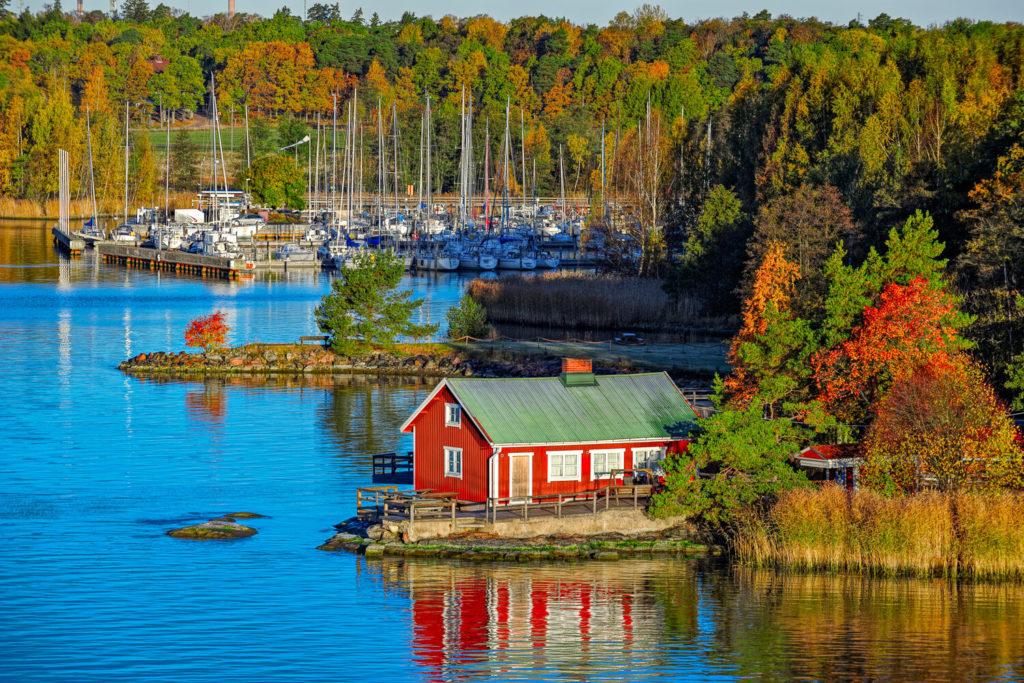 Ein rotes Haus auf einer der großen Inseln vor Turku mit einem Yachthafen im Hintergrund.