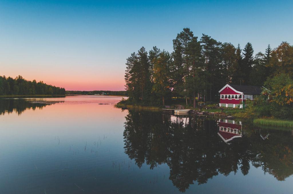 Blick über das Wasser bei Sonnenuntergang bei Umea. An Land rechts ist ein kleines rotes Haus zu erkennen, vor dem ein Boot im Wasser liegt.